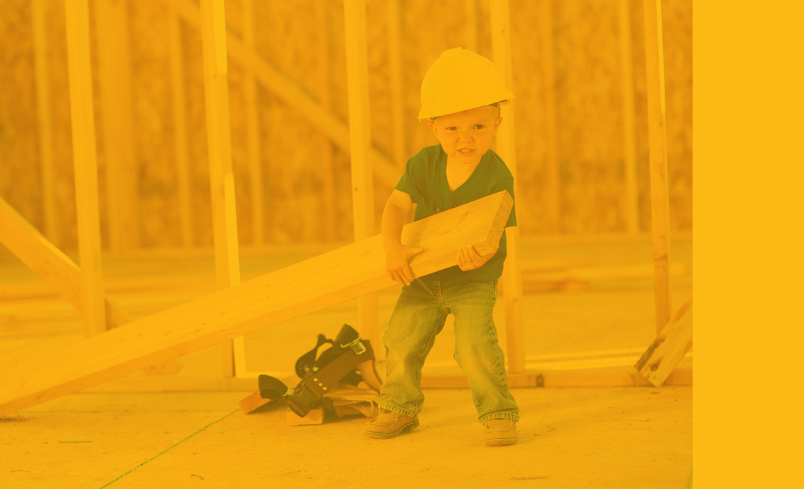 Web banner picture of little boy holding wood at a construction site to go with the tool kit as the free checking account gift.